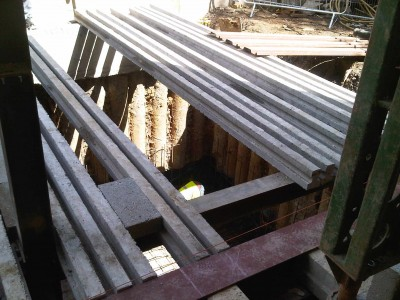 The load of the existing house wall, is transferred through steel columns down onto the floor slab, and the block and beams cover the basement, and can then be built off.