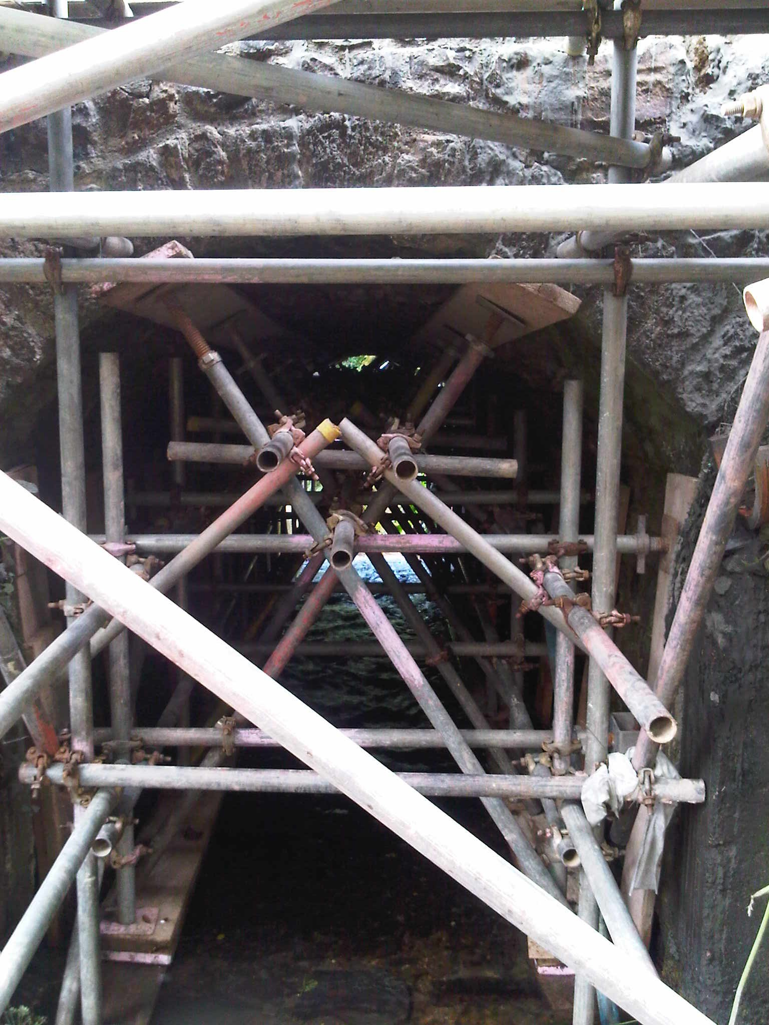 Scaffolding supports arch bridge while works continue on top.