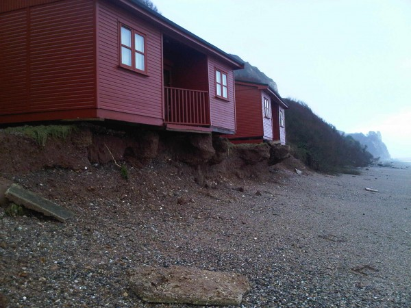 Branscombe, Devon, eroded beach chalets.
